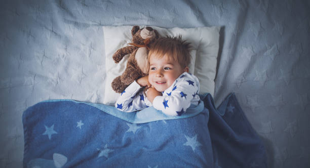 three years old child sleeping in bed stock photo