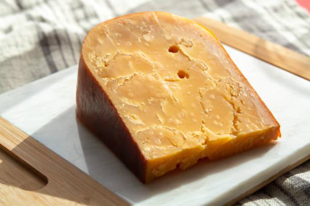 drie jaar oud donkergeel hard hollandse kaas in zonnelampen - beemster stockfoto's en -beelden