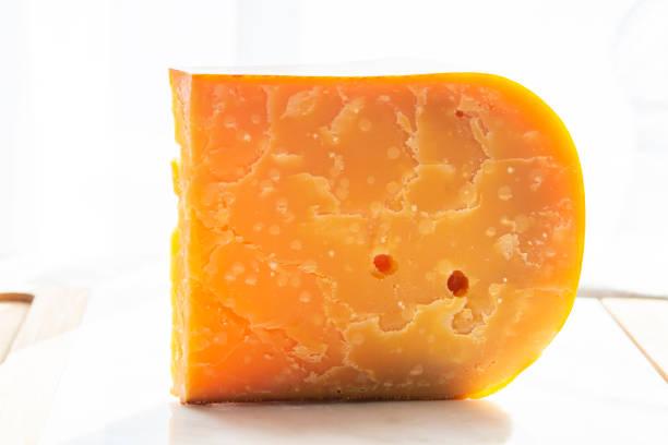 drie jaar oude donker gele harde nederlandse kaas in zonne lichten - beemster stockfoto's en -beelden