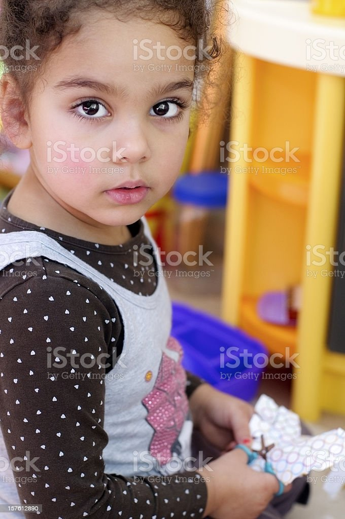Three Years Old Girl Cutting Paper Using Scissors stock photo