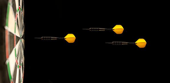Three Yellow Airborne Darts on a Dartboard Target