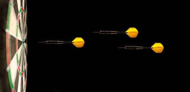 Three Yellow Airborne Darts on a Dartboard Target stock photo