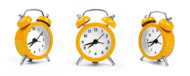 tres despertadores amarillos sobre blanco - clock fotografías e imágenes de stock
