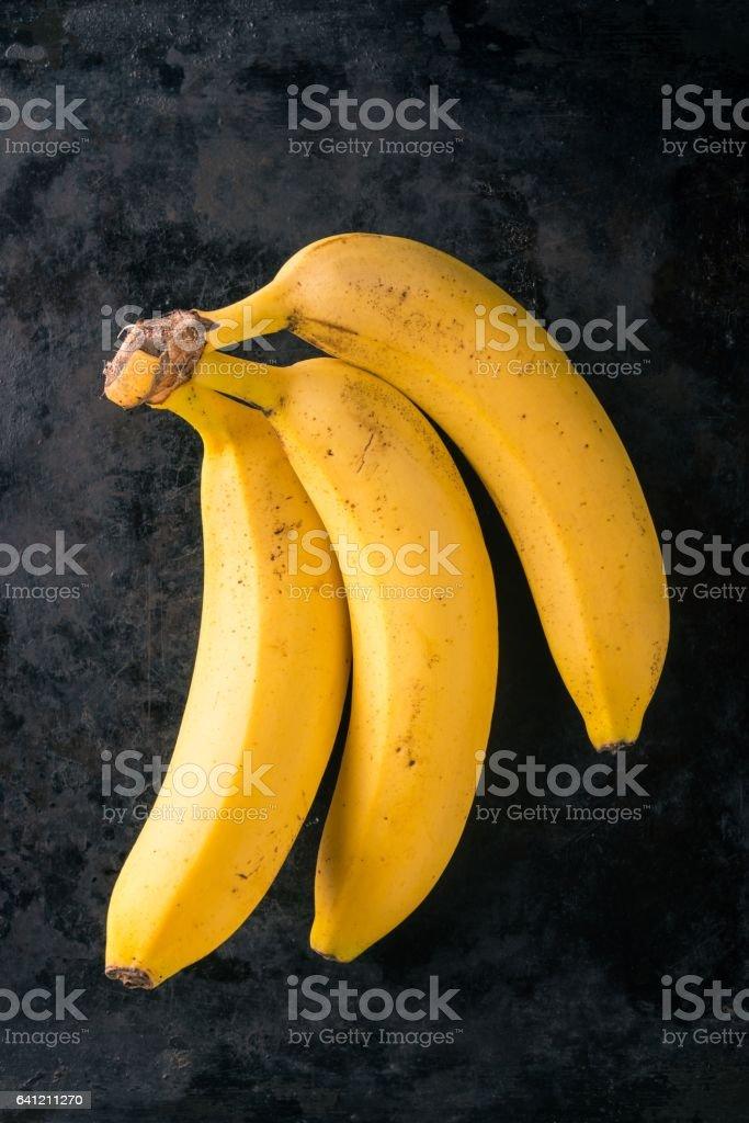 Three yellow bananas on dark worn tray stock photo