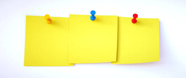 Three yellow blank sticky notes pinned to a white background. Suitable for additional composition. stock photo