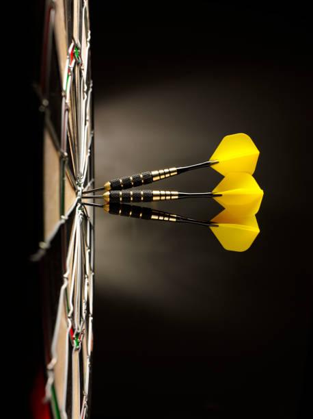 Three Yellow Darts in a Dartboard stock photo