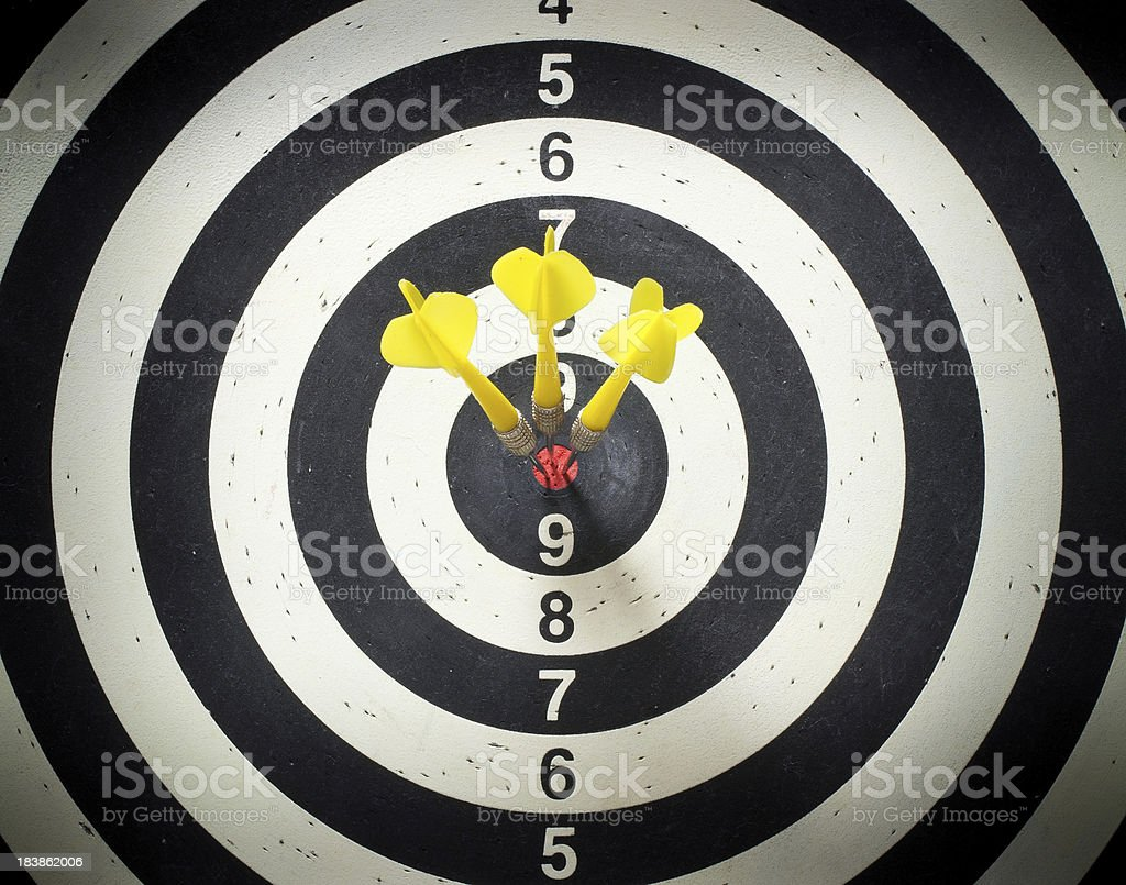 Three yellow darts in the black and white dartboard bullseye stock photo