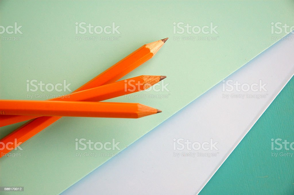 three yellow number 2 pencils and blue paper stock photo