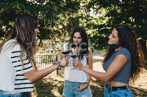 Three young adult friends are toasting with a glass of red wine. They are wearing protective facemasks due to the Coronavirus Covid-19 pandemic.