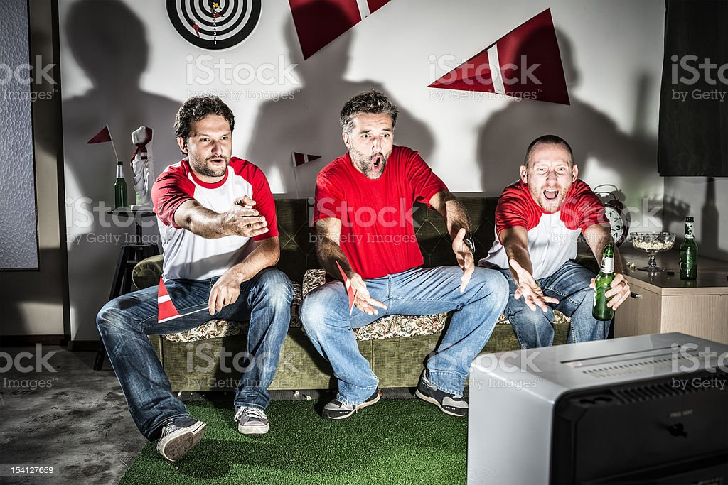 Three young adult men friends watching football: Missed goal disappointment stock photo