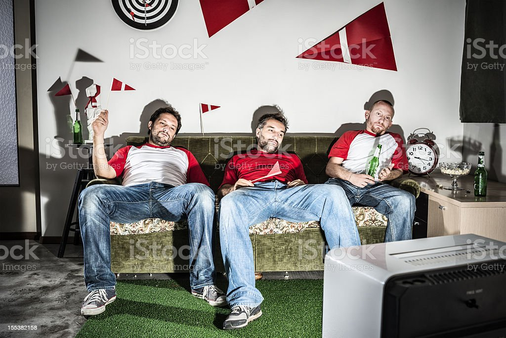 Three young adult men friends watching football on television: Defeat stock photo