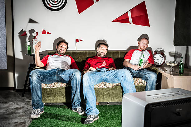 Three young adult men friends watching football on television: Defeat Three young adult men friends watching football on television: Defeat man cave couch stock pictures, royalty-free photos & images