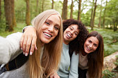 Three young adult women taking a selfie in a forest during a hike, close up