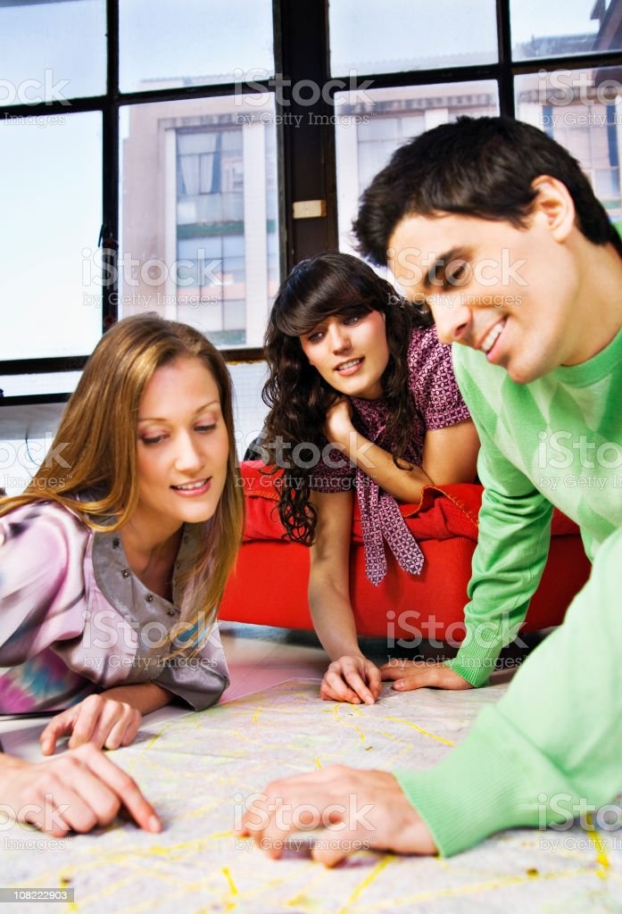 Three Young Adults Sitting on Floor and Looking at Map royalty-free stock photo