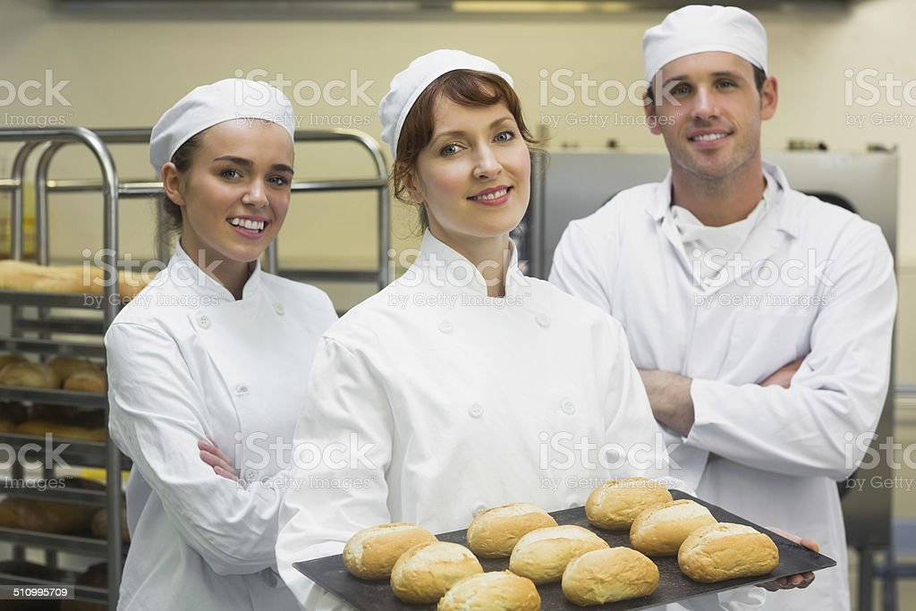 Three young bakers posing in a kitchen stock photo