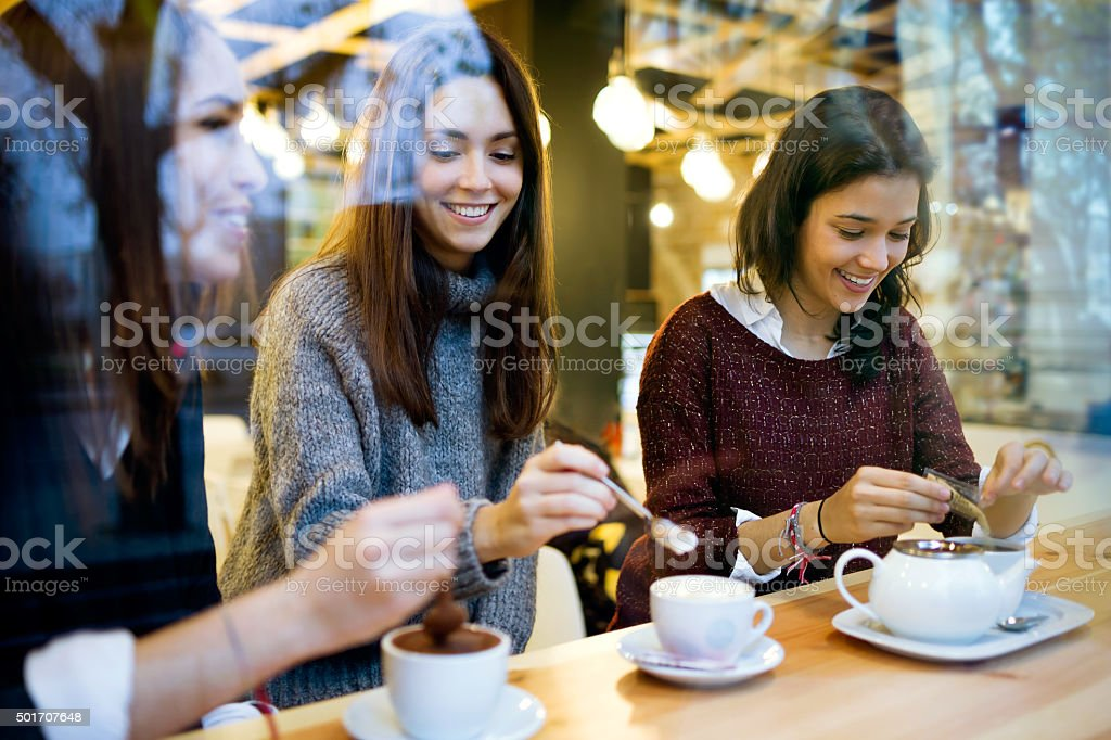 Three young beautiful women drinking coffee at cafe shop. stock photo