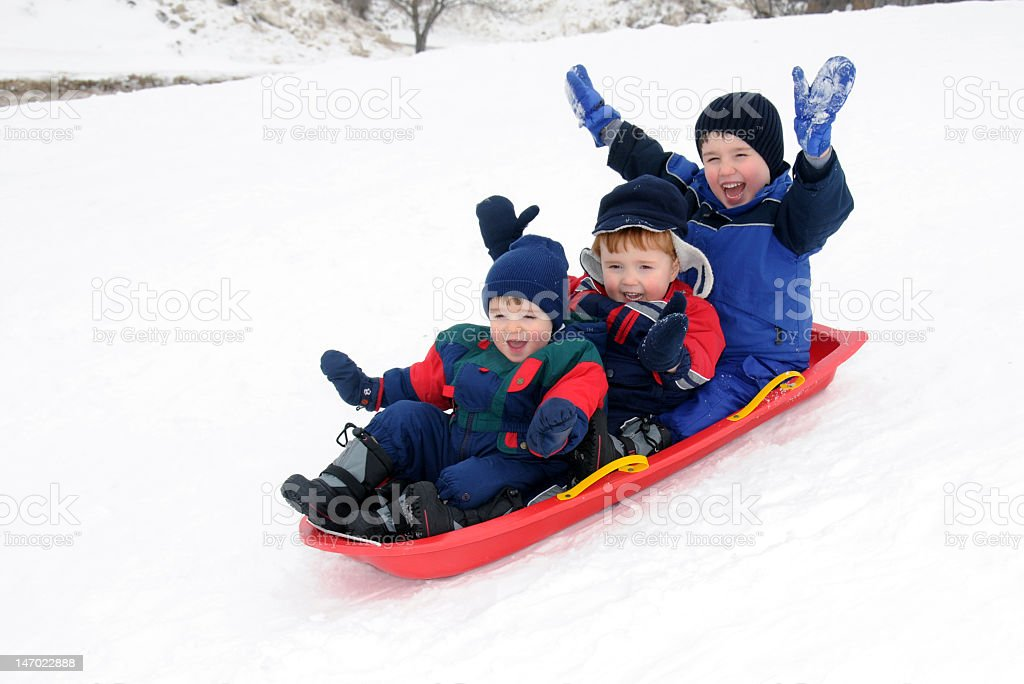 Three young boys ride a sled down a snowy hill, arms raised stock photo
