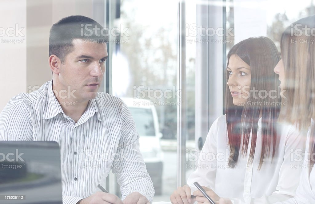 Three young business people discussing royalty-free stock photo