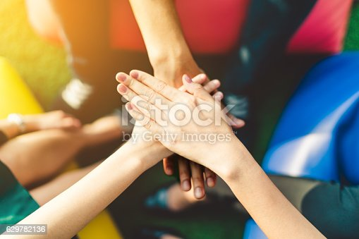 istock Three young business people joining hands, teamwork concept 629782136