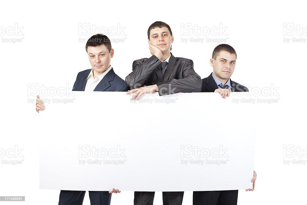 Drei junge Geschäftsleute halten ein großes leeres Schild – Foto
