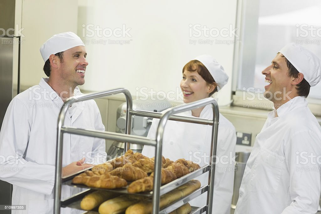 Three young chatting bakers standing in a kitchen stock photo