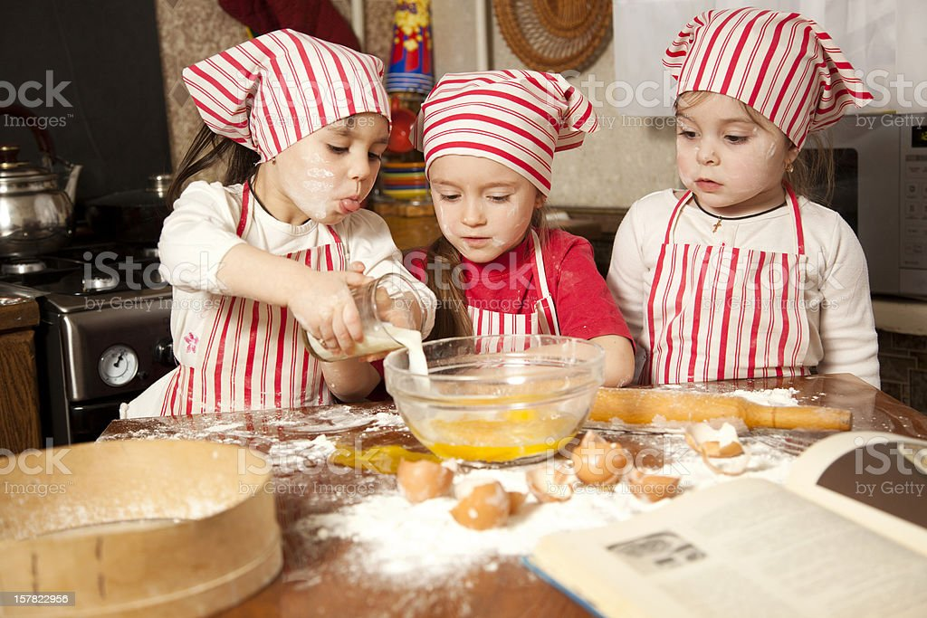 Three young children baking in the kitchen stock photo