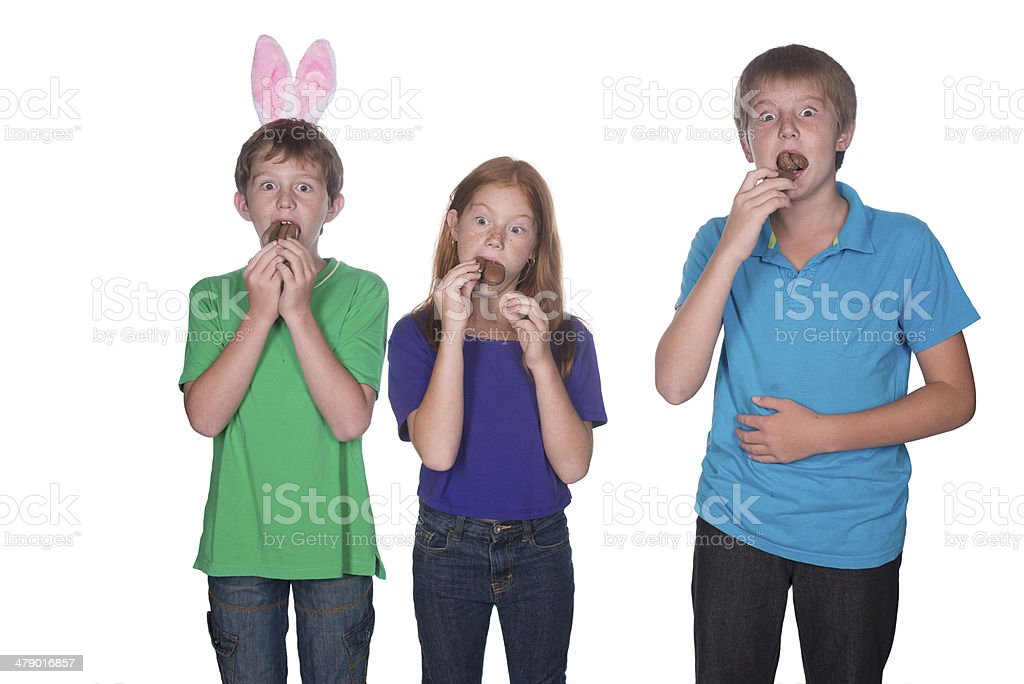 three young children eating easter eggs stock photo