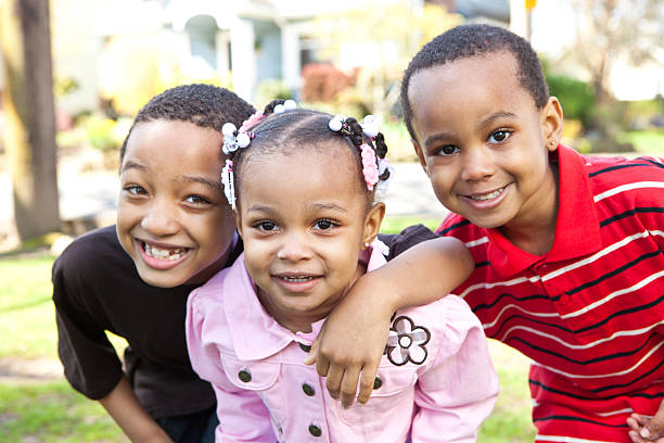 Three young children outside smiling at camera stock photo