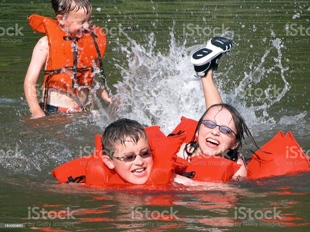 Three Young Children Playing and Swimming with Life Vests stock photo
