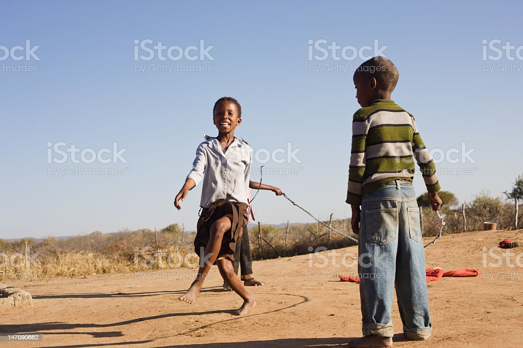 Three young children playing with a skipping rope stock photo