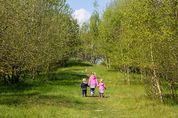 three young children walking hand in hand - three roads uphill bildbanksfoton och bilder