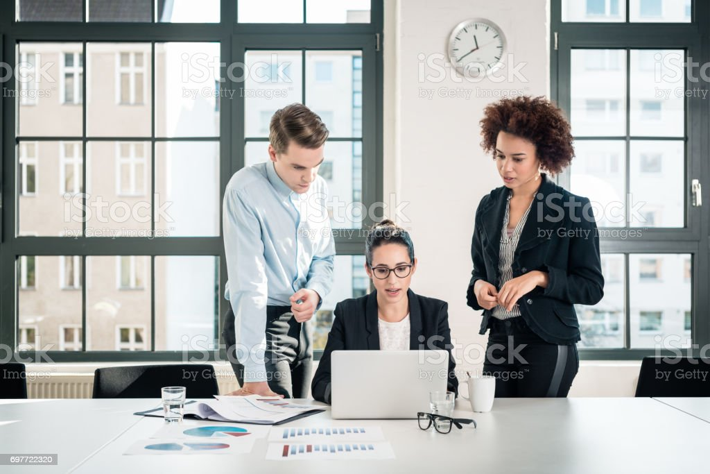 Three young colleagues talking during break in the meeting room stock photo