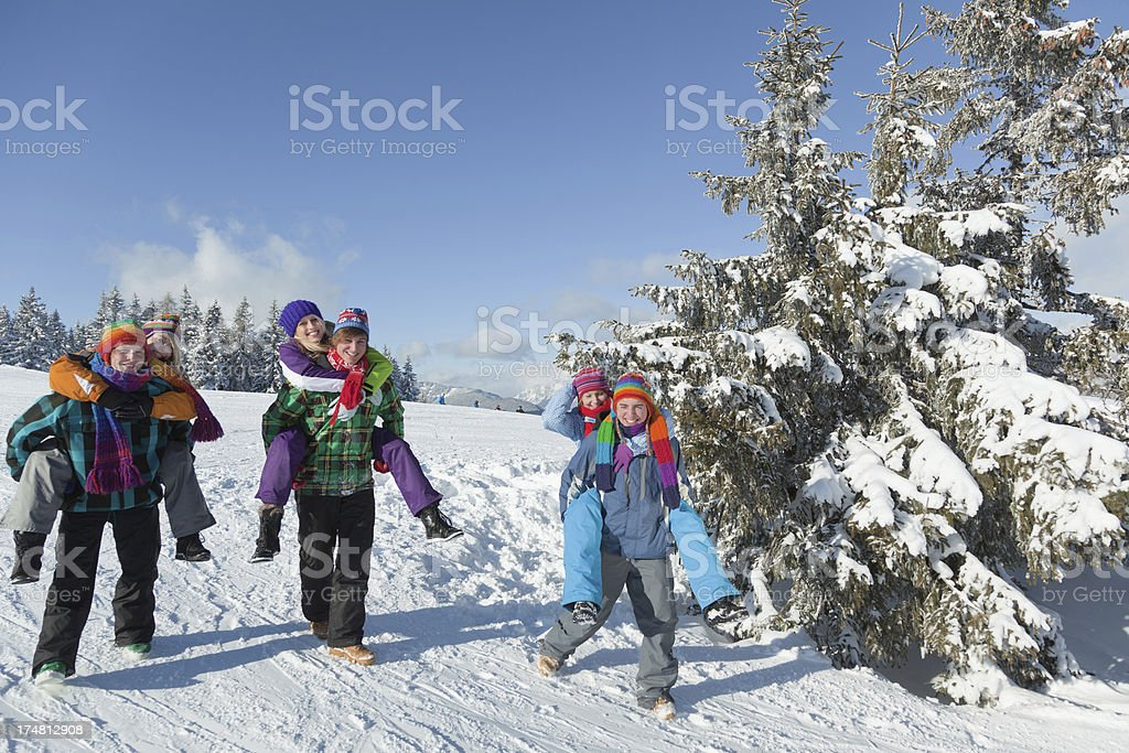 Three young couples walking piggyback in winter landscape royalty-free stock photo