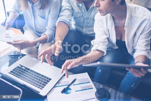 istock Three young coworkers working on mobile laptop computer at office.Young woman holding tablet and pointing on touch screen. Horizontal, blurred background. 907677886