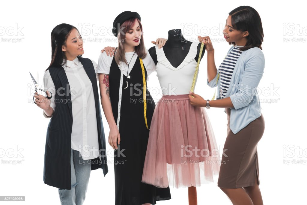 Three Young Fashion Designers Holding Scissors And Measuring Tapes While Working With Dress On Dummy Stock Photo Download Image Now Istock