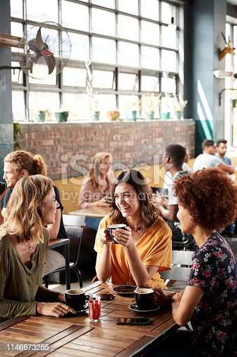 Three Young Female Friends Meeting Sit At Table In Coffee Shop And Talk