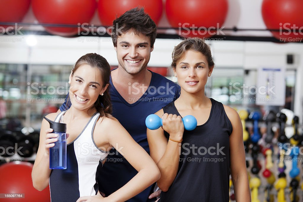 Three young fit people in a fitness club royalty-free stock photo