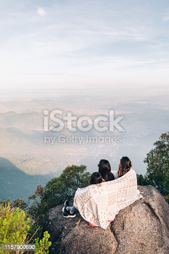 Three young friends enjoying the view from the mountain