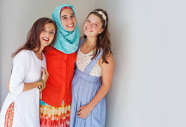 three young friends of different religions Three young girls standing happily together in the corner hindu muslim stock pictures, royalty-free photos & images