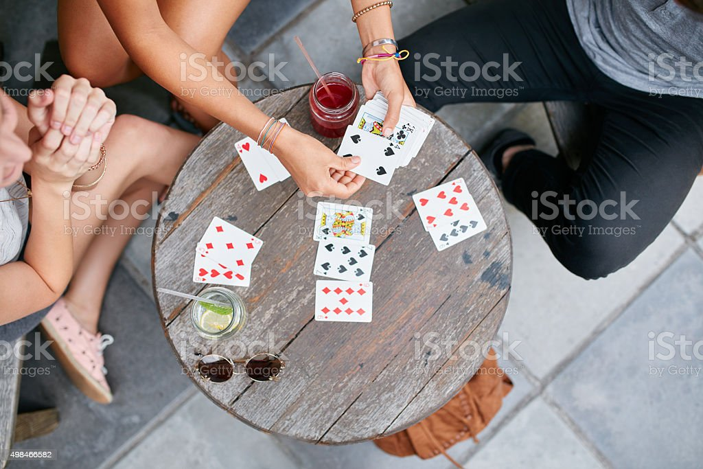 Three young friends playing cards at cafe stock photo