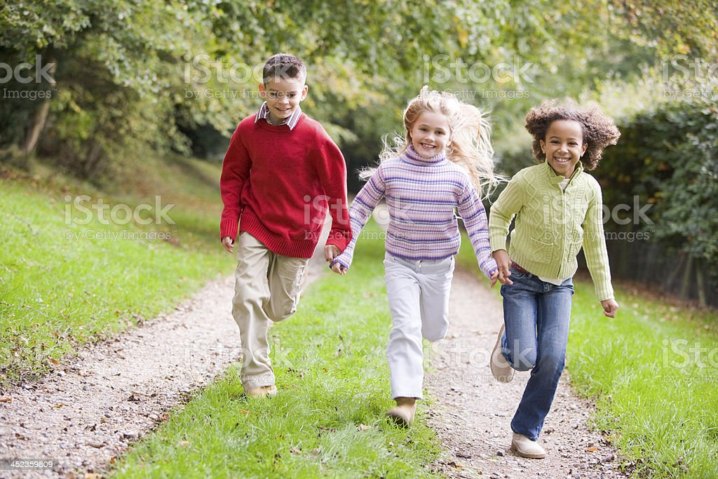 Three young friends running on a path outdoors smiling royalty-free stock photo