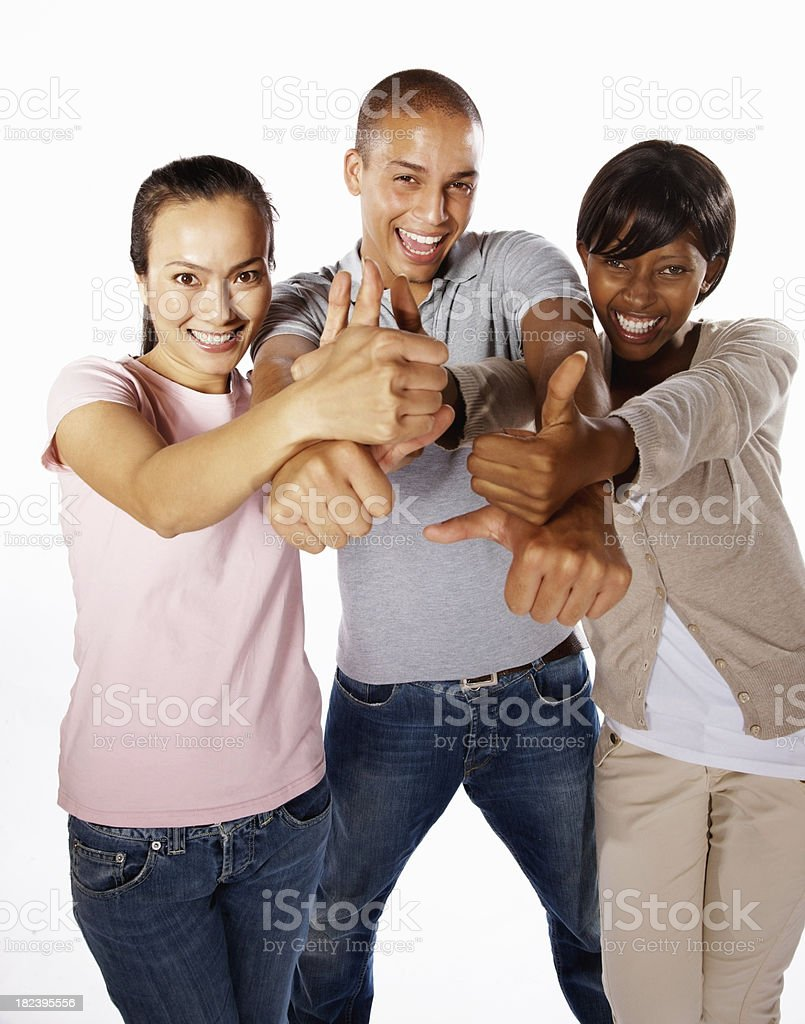 Three young friends showing thumbs up sign royalty-free stock photo