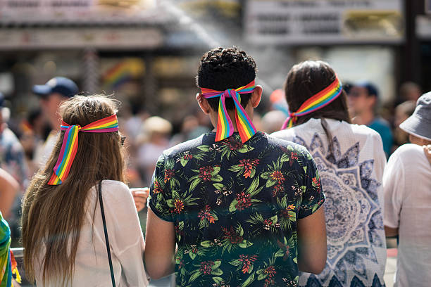 three young friends standing in a crowd celebrating pride parade. - modefarben sommer 2016 stock-fotos und bilder
