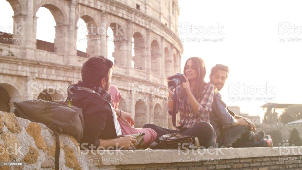 Trois jeunes amis touristes assis couché devant le Colisée à rome au coucher du soleil à prendre des photos photos avec dslr caméra sacs à dos lunettes de soleil heureux belle fille cheveux longs slow motion - Photo