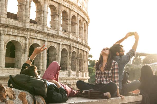 drei junge freunde touristen sitzen liegen im vordergrund des kolosseums in rom selfie fotografieren mit smartphone-kamera. sonnenuntergang mit blendenfleck - schönste reiseziele der welt stock-fotos und bilder