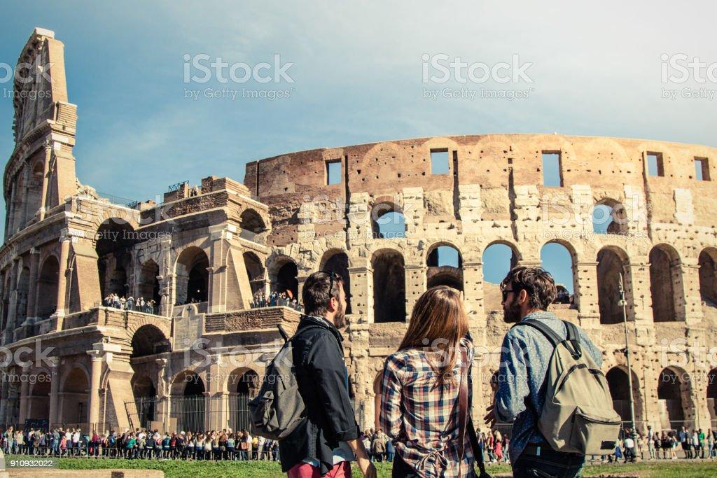 Tres turistas jóvenes amigos parado frente a Coliseo de Roma con mochilas gafas pelo largo chica hermosa feliz. Destello de lente - foto de stock