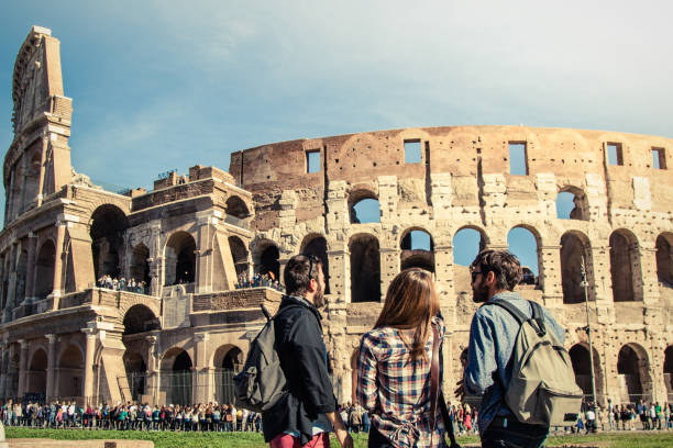 Three young friends tourists standing in front of colosseum in rome with backpacks sunglasses happy beautiful girl long hair. Lens flare stock photo