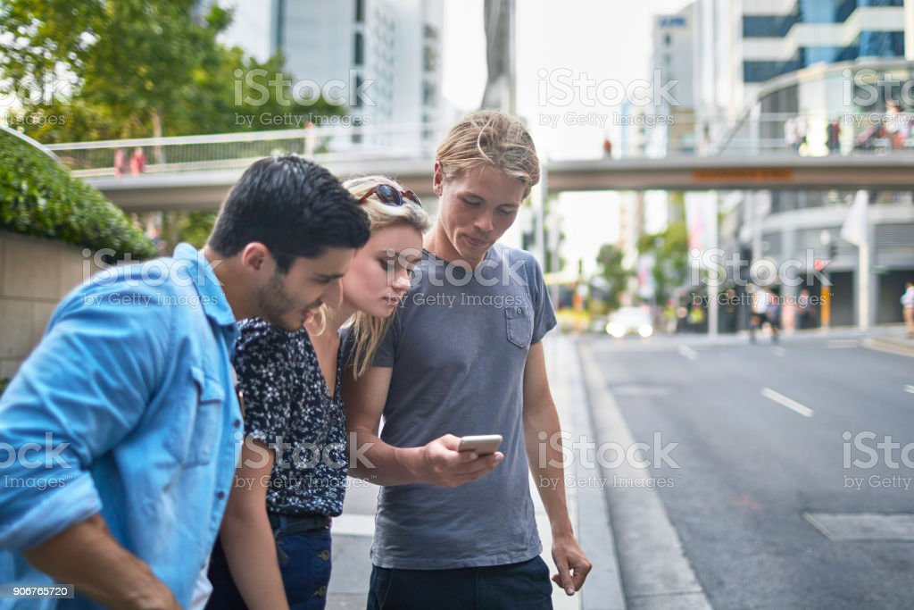 Three young friends waiting for a crowdsourced taxi in Sydney stock photo