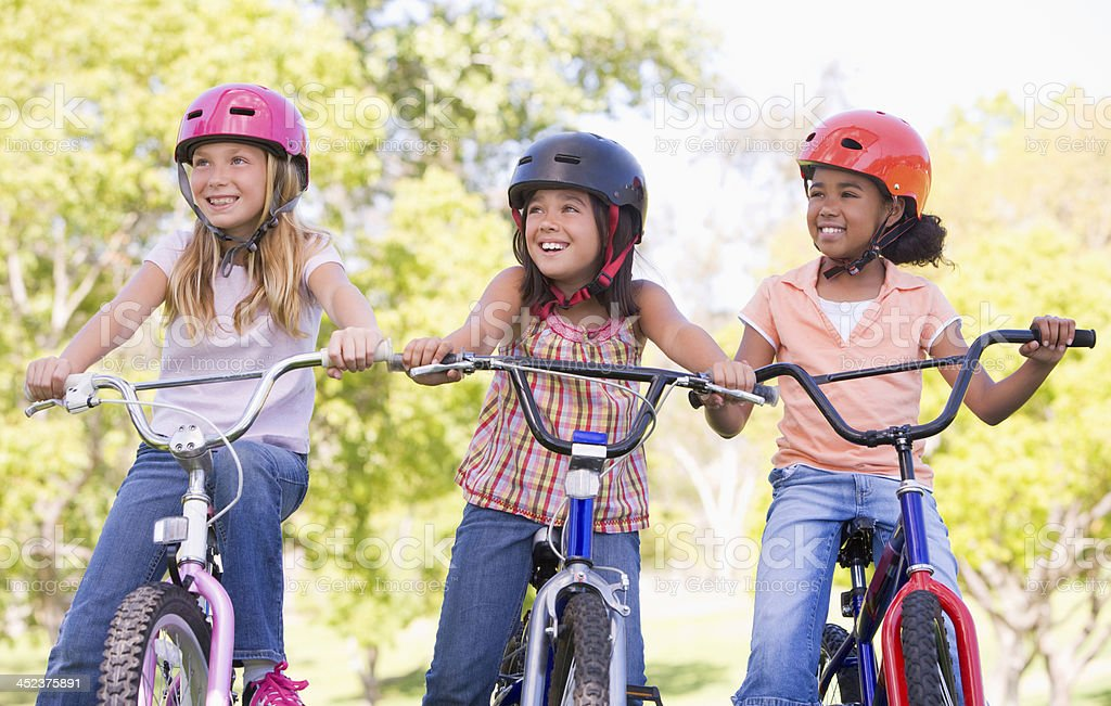 Three young girl friends outdoors on bicycles smiling stock photo