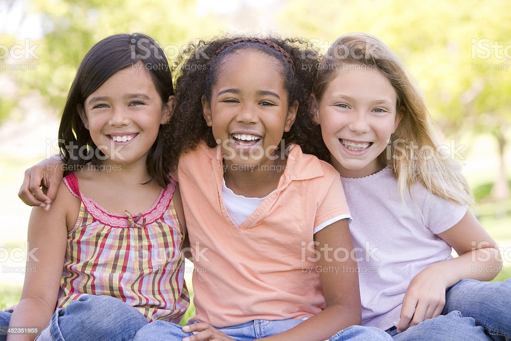 Three young girl friends sitting outdoors smiling royalty-free stock photo